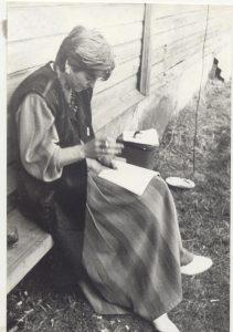 """Su apysakos """"Rudens dienos užkalbėjimas"""" rankraščiu ant kelių. Mozūriškiai (Kauno raj.), 1989 m."""