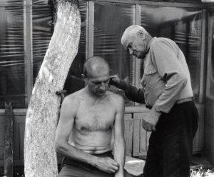 Tėvas Pranas kerpa savo sūnų Petrą namų (Šiauliai, Ragainės gatvė 50) kieme. Fotografavo Ričardas Šileika. 2003 metų rugpjūtis