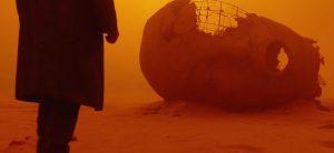 Pagrindinis veikėjas K, žengiantis postapokaliptine dykuma.