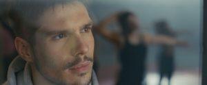 Tony (François Civil) pro stiklą stebi savo buvusią mylimąją Leylą.