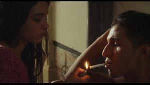 Fotografė Amel (Hafsia Herzi) pridega cigaretę savo pirmajam modeliui.