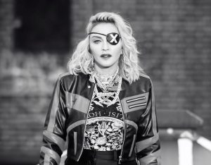 """Akies raištis su X ženklu lydi beveik visus Madonnos pasirodymus. Jis žymi albumo """"Madame X"""" erą, lygiai kaip auksinis dantis neatsiejamas nuo albumo """"Erotica"""" (1992)."""
