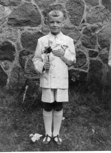 1958 metai. Rimantas Vanagas Pirmosios komunijos dieną Anykščių šventoriuje. Asmeninio archyvo nuotrauka